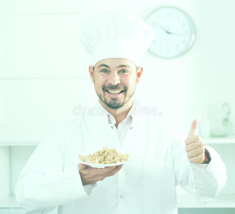 Junger glücklicher europäischer Koch in Angebothaferbrei der Kappe für Bruch stockbilder