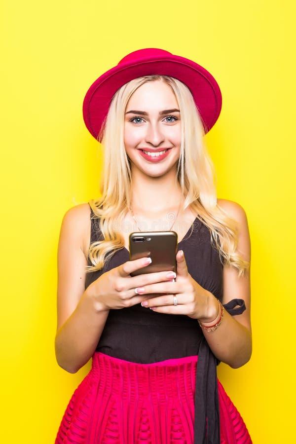 Junger glücklicher Frauengebrauch mit Handy auf dem gelben Wandhintergrund lizenzfreies stockbild