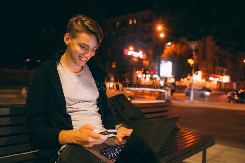 Junger glücklicher Freiberufler, der in der Stadtstraße arbeitet stockbilder