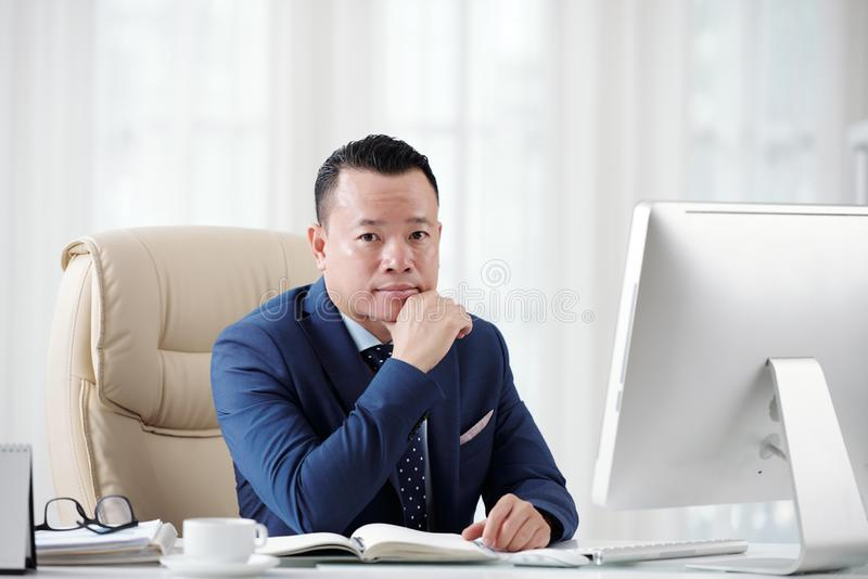 Junger glücklicher Geschäftsmann, arbeitend am Schreibtisch lizenzfreies stockbild