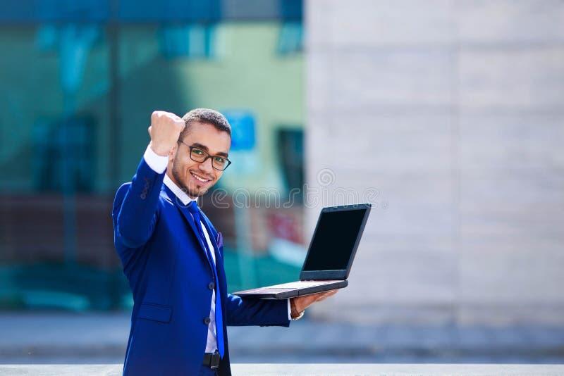 Junger glücklicher Geschäftsmann, der auf Bürogebäudehintergrund w steht lizenzfreies stockbild