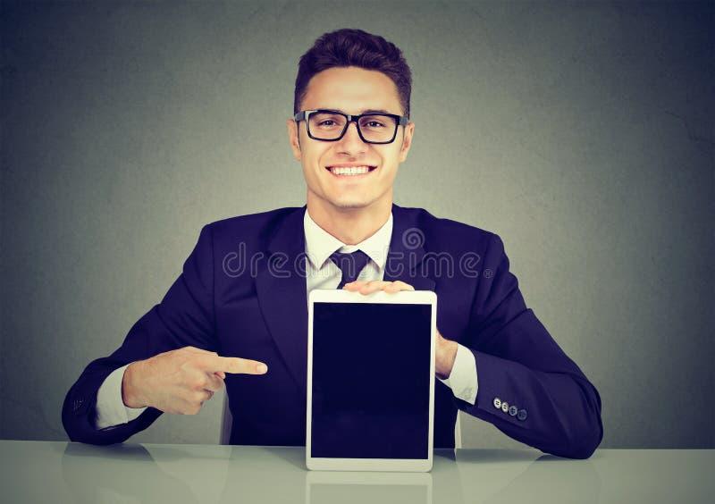 Junger glücklicher Geschäftsmann, der eine Tablette zeigt stockfotos