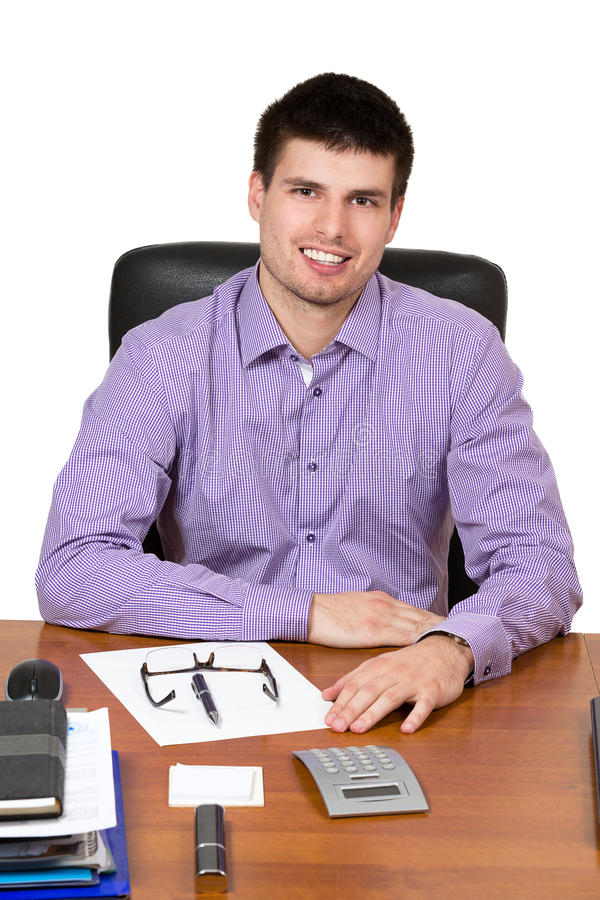 Junger glücklicher Geschäftsmann, der an seinem Schreibtisch arbeitet lizenzfreie stockfotos