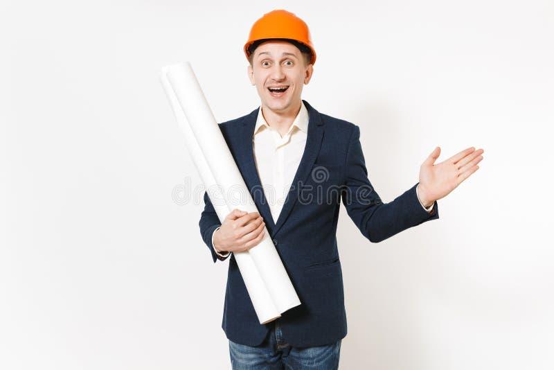 Junger glücklicher Geschäftsmann im dunklen Anzug, schützender Hardhat, der Planpläne hält und beiseite Hand auf Kopienraum zeigt lizenzfreie stockfotografie