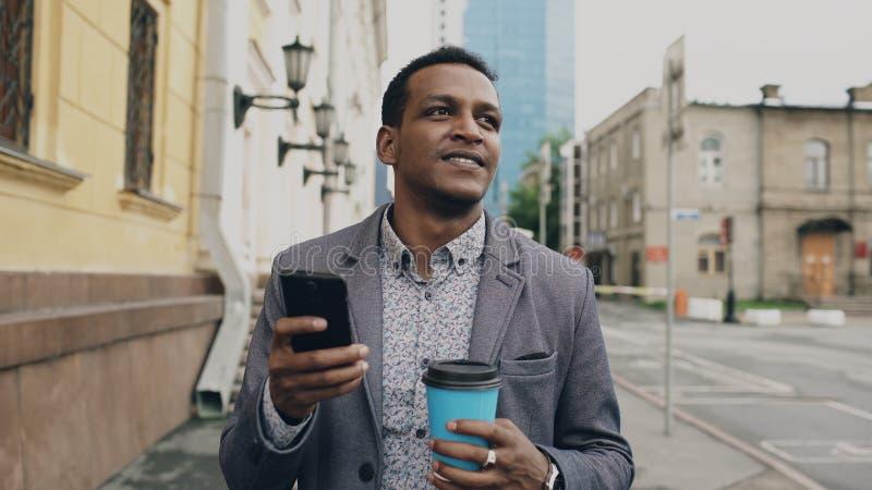 Junger glücklicher Geschäftsmann unter Verwendung des Smartphone und mit Tasse Kaffee draußen gehen lizenzfreie stockfotografie
