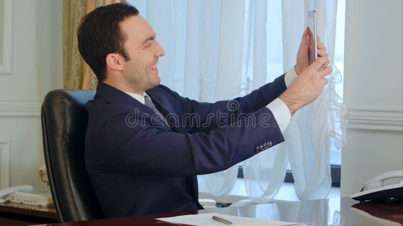 Junger glücklicher Geschäftsmannmann, der lustige selfies mit digitaler Tablette im Büro nimmt lizenzfreie stockbilder