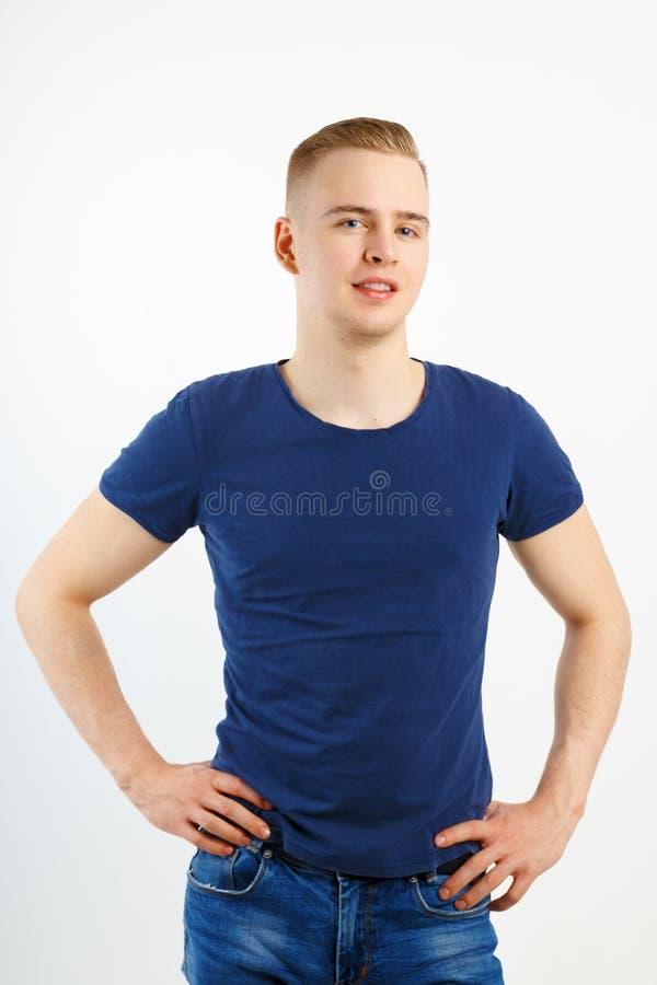 Junger glücklicher gutaussehender Mann in den blauen Hemd- und Jeanshaltungen lizenzfreie stockbilder