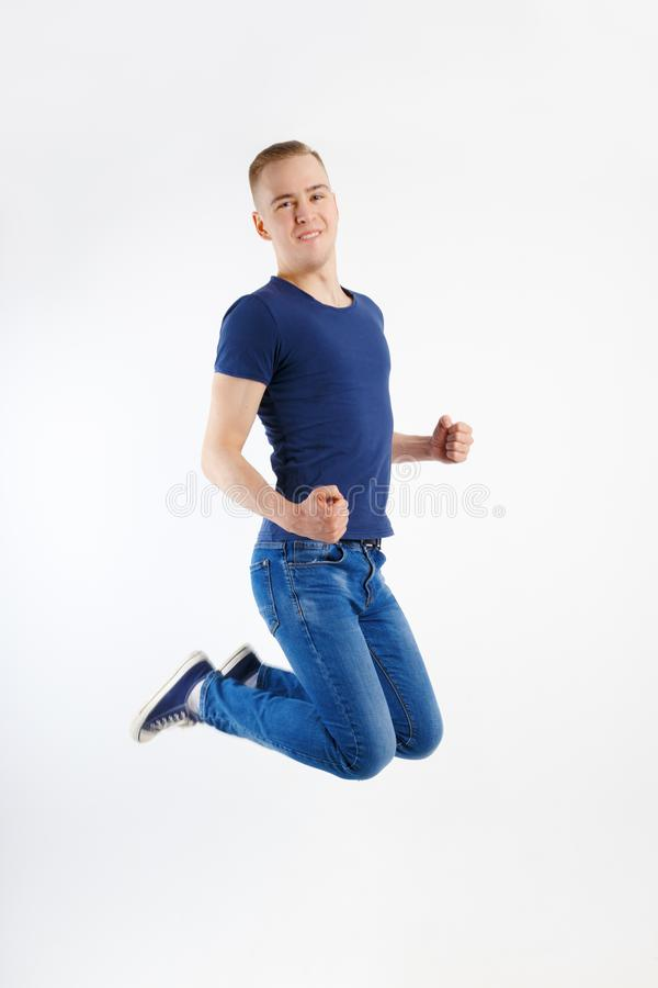 Junger glücklicher gutaussehender Mann im blauen Hemd und in den Jeans springt stockfotografie