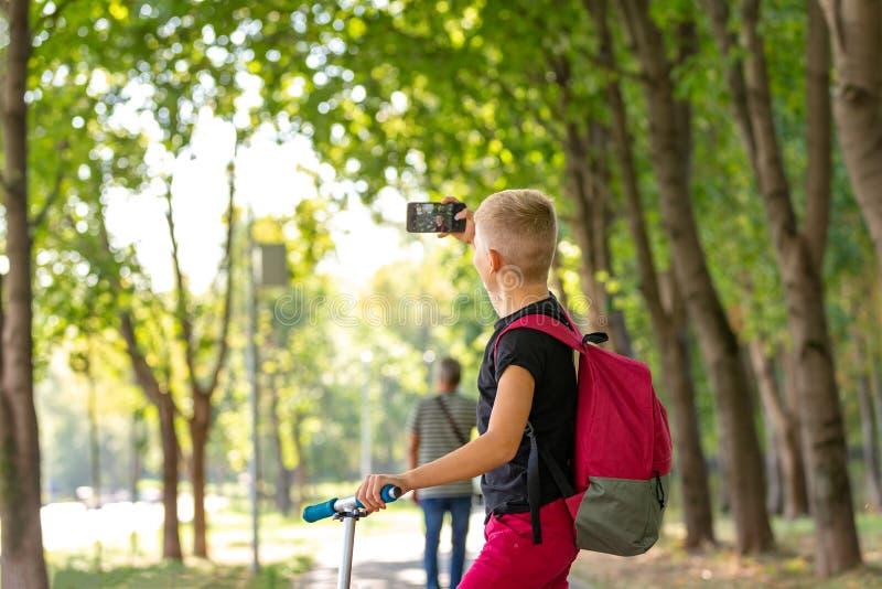 Junger glücklicher jugendlicher Junge, der einen Roller am warmen sonnigen Sommertag im Park reitet und selfie auf smartpone wann stockbild