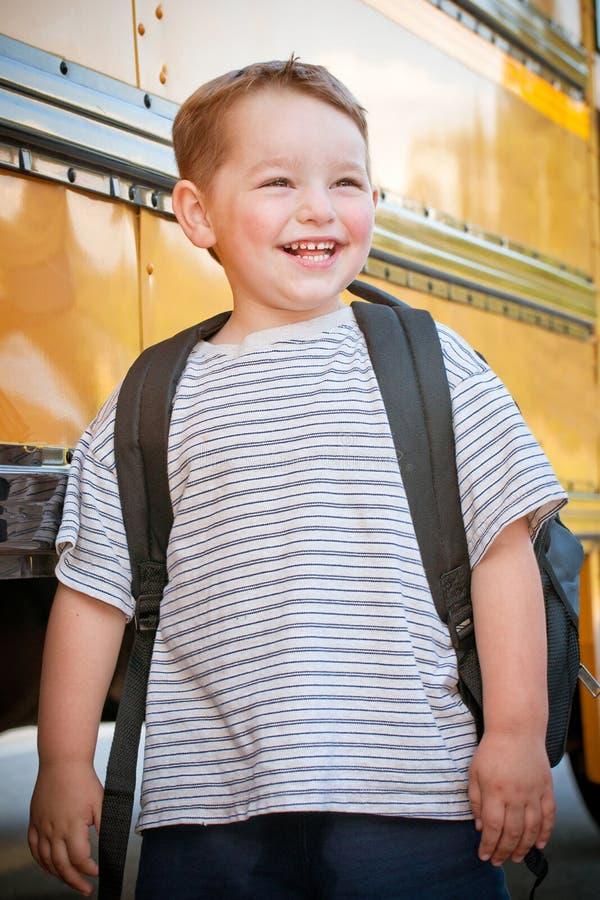 Junger glücklicher Junge wartet, um Bus für Schule einzusteigen stockfotografie