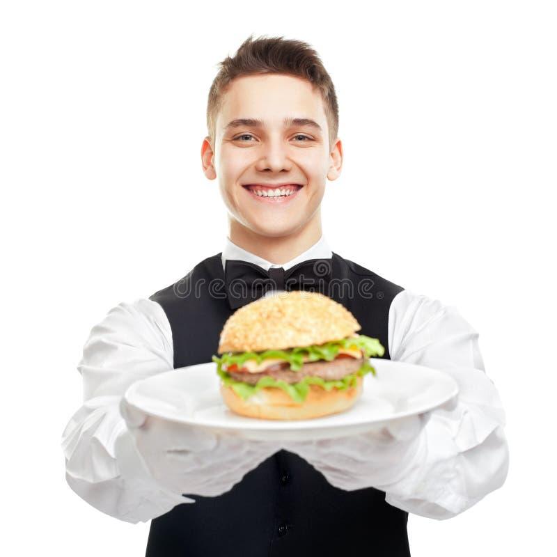 Junger glücklicher lächelnder Kellner, der Hamburger auf Platte hält stockbild
