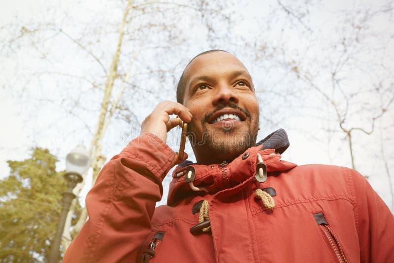 Junger glücklicher lächelnder städtischer Hippie-Mann, der informelle Kleidung trägt und intelligentes Telefon verwendet Hippie,  stockfotos