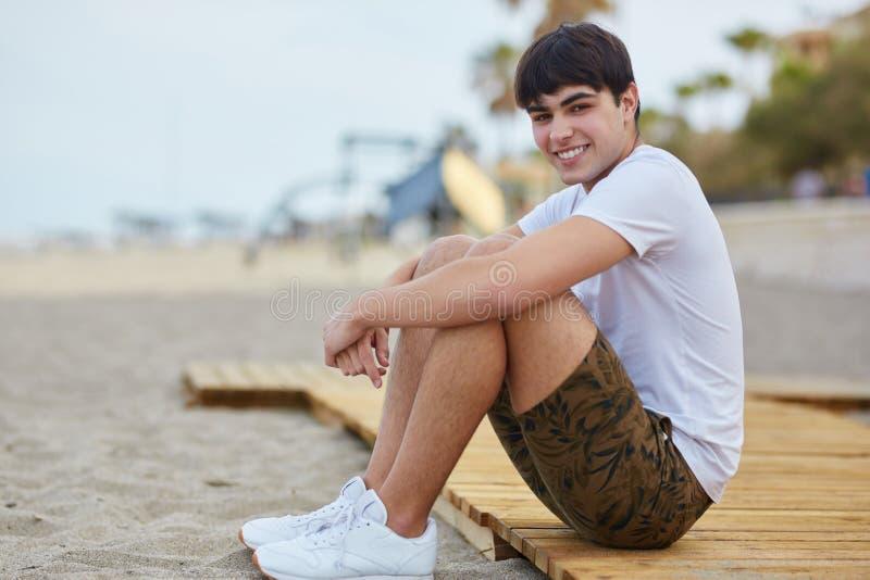 Junger glücklicher Mann, der auf dem Strandlächeln sitzt lizenzfreies stockbild