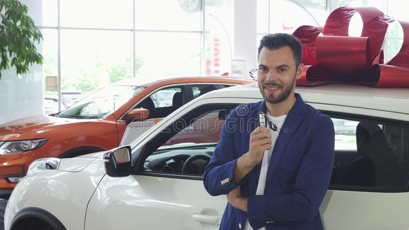 Junger glücklicher Mann, der Autoschlüssel zu seinem neuen Automobil zeigend lächelt stockbild