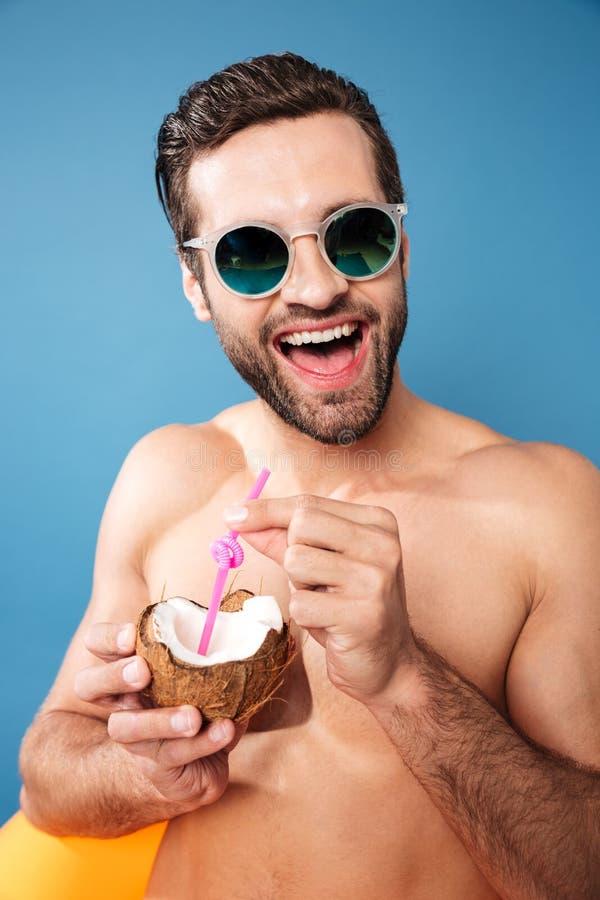 Junger glücklicher Mann, der Cocktail von den Cocos hält stockfotografie