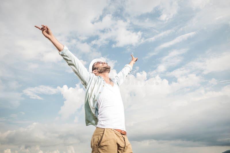Junger glücklicher Mann, der das gute Wetter genießt stockbild