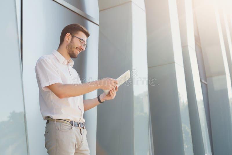 Junger glücklicher Mann, der draußen Tablette verwendet lizenzfreies stockfoto