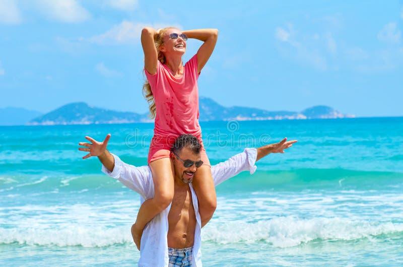 Junger glücklicher Mann, der einer lachenden Frau eine Doppelpolfahrt gibt stockfotografie