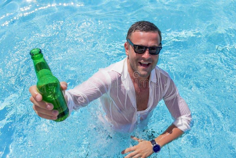 Junger glücklicher Mann, der im Swimmingpool partying ist stockbilder