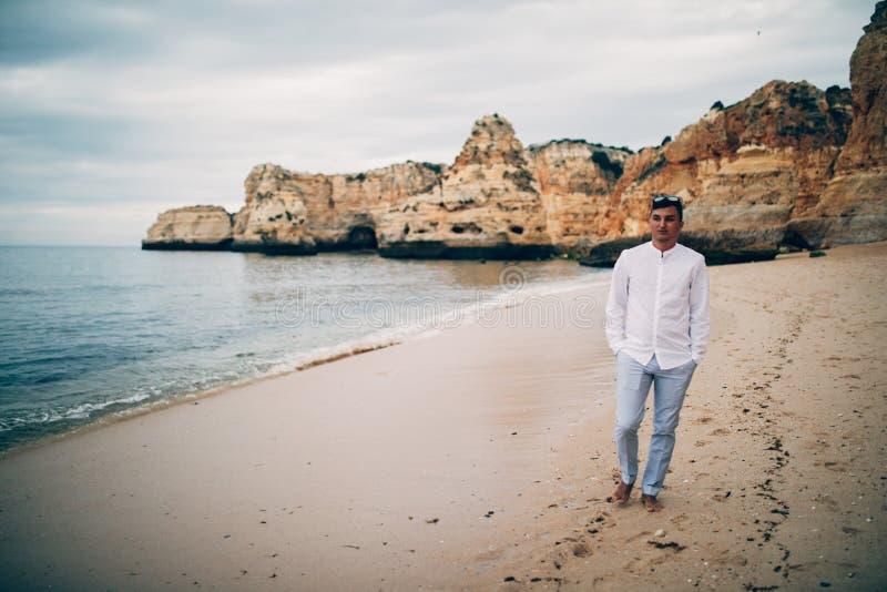 Junger glücklicher Mann, der in J ein weißes Hemd auf dem Strand und das Meer bei Sonnenuntergang geht lizenzfreie stockfotos