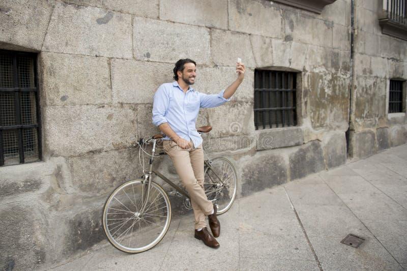 Junger glücklicher Mann, der selfie mit Handy auf Retro- kühlem Weinlesefahrrad nimmt lizenzfreie stockfotografie