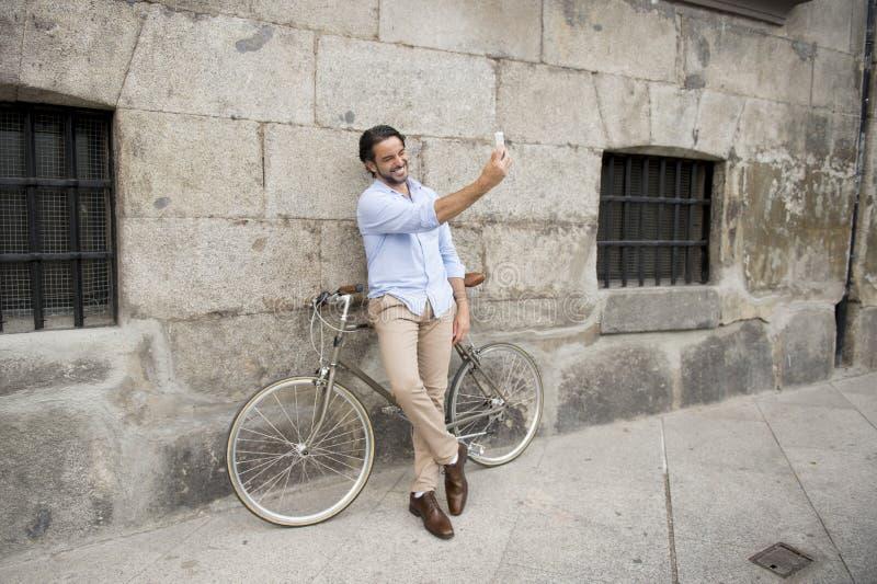 Junger glücklicher Mann, der selfie mit Handy auf Retro- kühlem Weinlesefahrrad nimmt stockbild