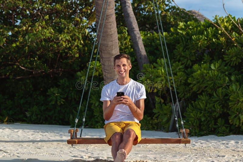 Junger glücklicher Mann gesetzt auf einem Schwingen und der Anwendung seines Telefons Weißer Sand und Dschungel als Hintergrund stockfotografie
