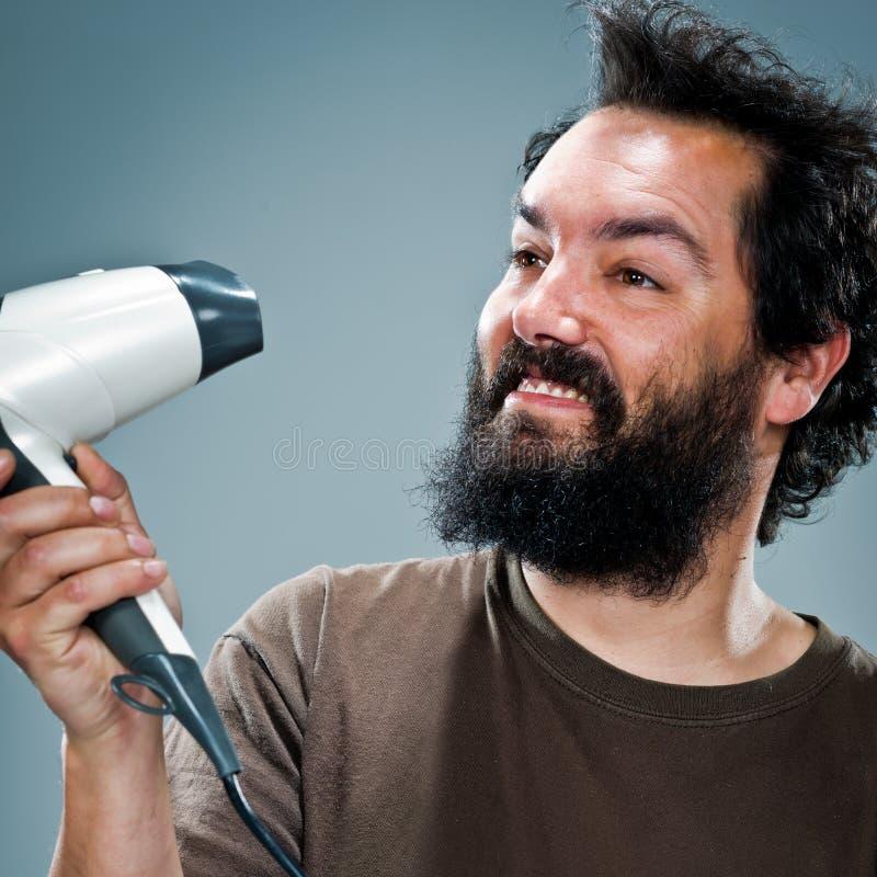 Junger glücklicher Mann mit einem Haartrockner lizenzfreies stockbild