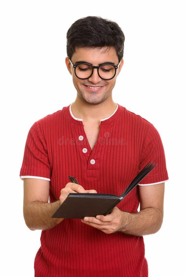 Junger glücklicher persischer Mann, der auf Tagebuch schreibt stockbild