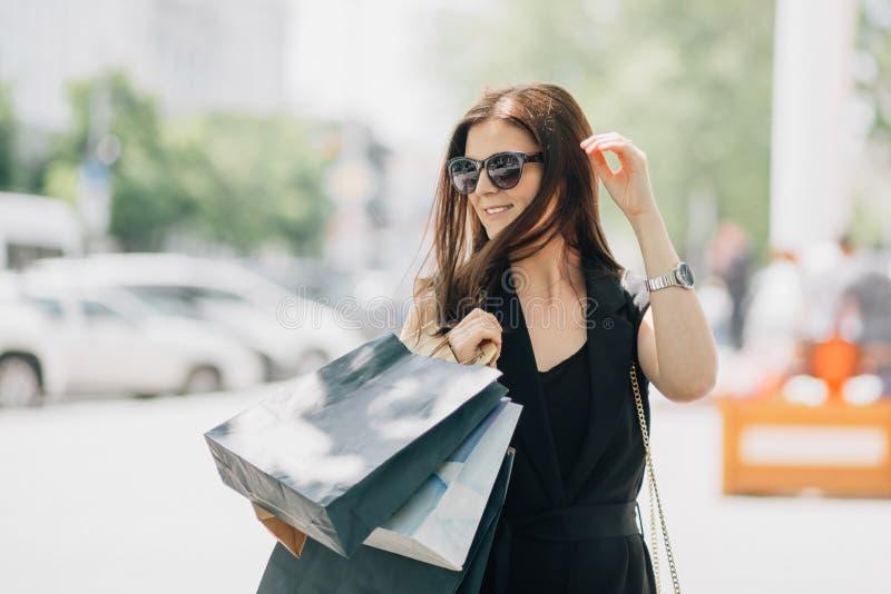 Junger glücklicher schöner kaukasischer Frau Brunette, der mit Einkaufstaschen auf der Straße lächelt lizenzfreie stockbilder