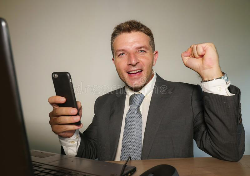 Junger glücklicher und attraktiver Geschäftsmann, der mit Handy am Bürocomputertisch herein feiert das Erfolgsgestikulieren aufge lizenzfreie stockfotografie