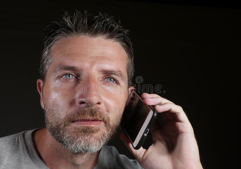 Junger glücklicher und attraktiver kaukasischer Mann, der am Handy hat das Geschäftsgespräch lokalisiert auf schwarzem Hintergrun lizenzfreies stockbild