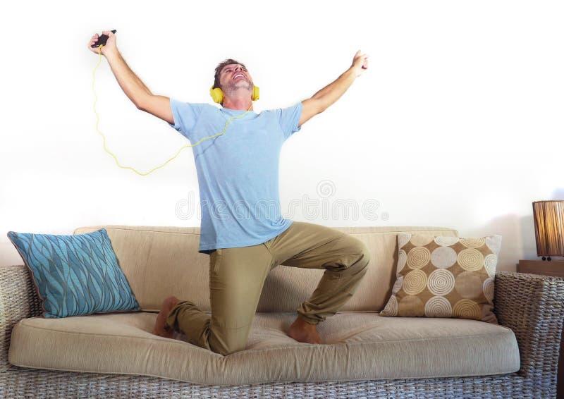 Junger glücklicher und aufgeregter Mann, der auf die Sofacouch hört Musik mit dem Handy und Kopfhörern singen und tanzen verrückt stockfoto