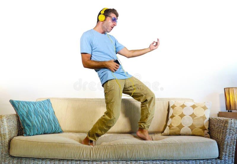 Junger glücklicher und aufgeregter Mann, der auf die Sofacouch hört Musik mit dem Handy und Kopfhörern spielen Luftgitarre verrüc lizenzfreies stockbild
