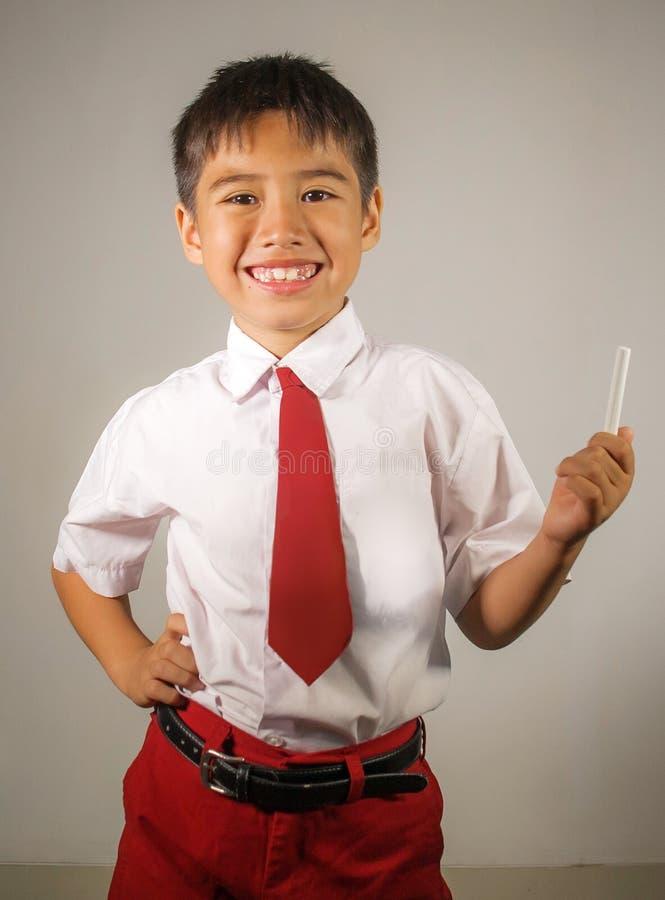 Junger glücklicher und aufgeregter Schüler in der Schuluniform, die das lächelnde nette Genießen der Kreide zurück zu Schule in d lizenzfreies stockfoto