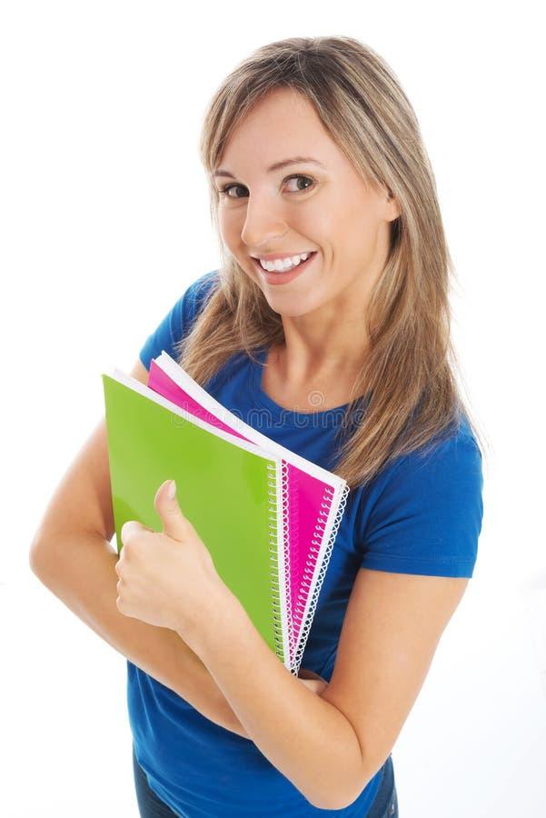 Junger glücklicher und erfüllter Student, der Arbeitsbuch hält. lizenzfreie stockbilder