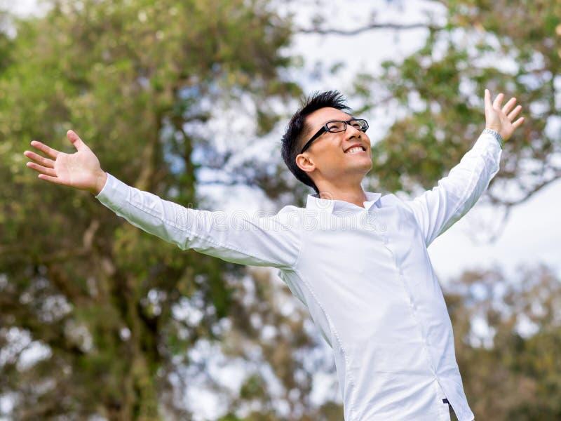 Junger glücklicher und erfolgreicher Geschäftsmann während seines Bruches im Park stockbild