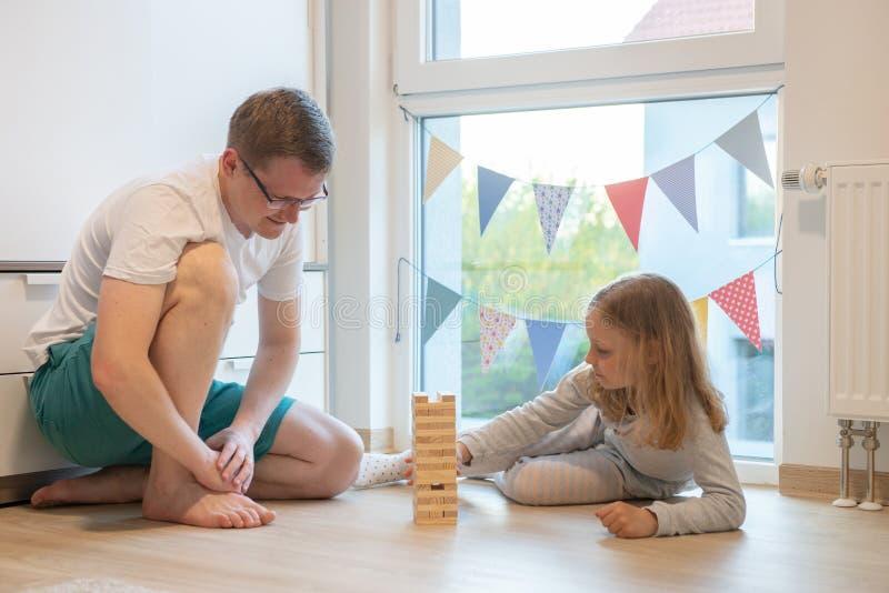 Junger glücklicher Vater, der mit seiner netten Tochter mit Holzklötzen spielt lizenzfreie stockfotografie