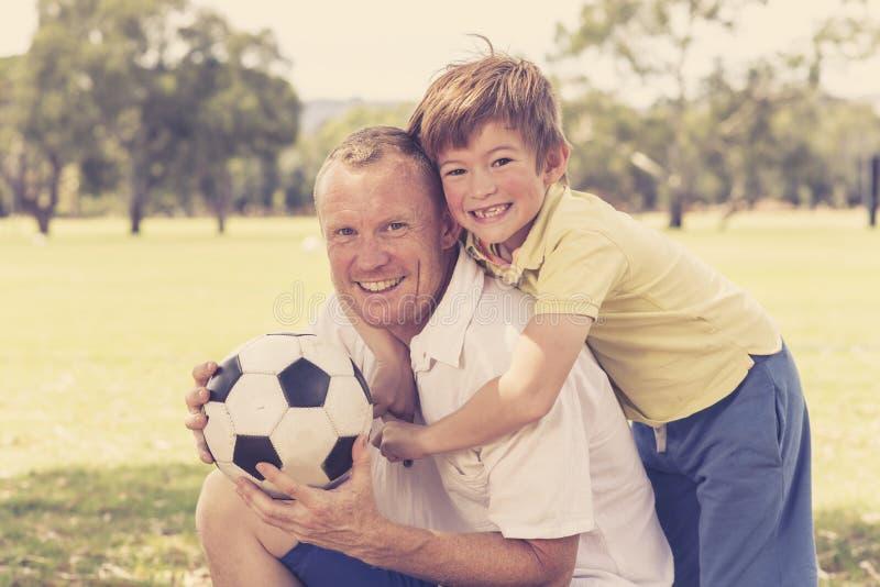 Junger glücklicher Vater und aufgeregte 7 oder 8 Jahre alte Sohn, die zusammen Fußballfußball auf dem Stadtparkgarten aufwirft sü stockfoto