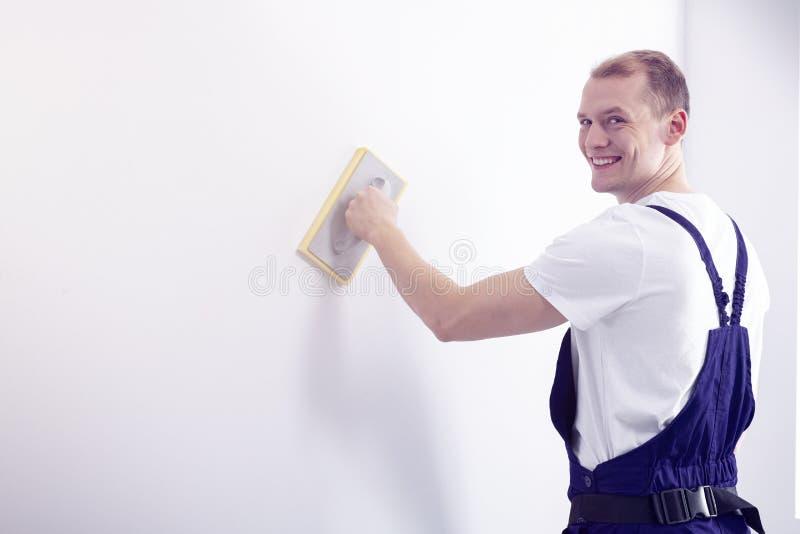Junger, glücklicher Wandmaler bei der Arbeitskleidungsaufstellung, den Nocken betrachtend lizenzfreies stockfoto