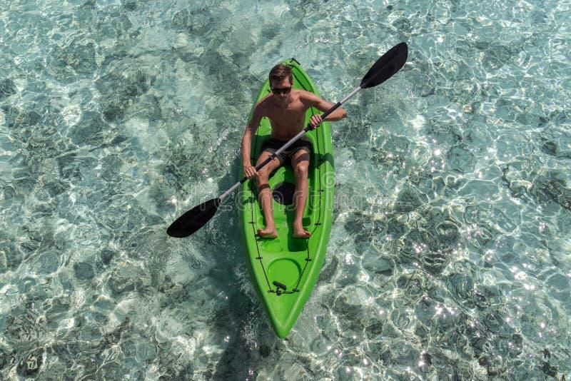 Junger gl?cklicher Mann, der auf einer Tropeninsel in den Malediven Kayak f?hrt Freies blaues Wasser lizenzfreie stockbilder