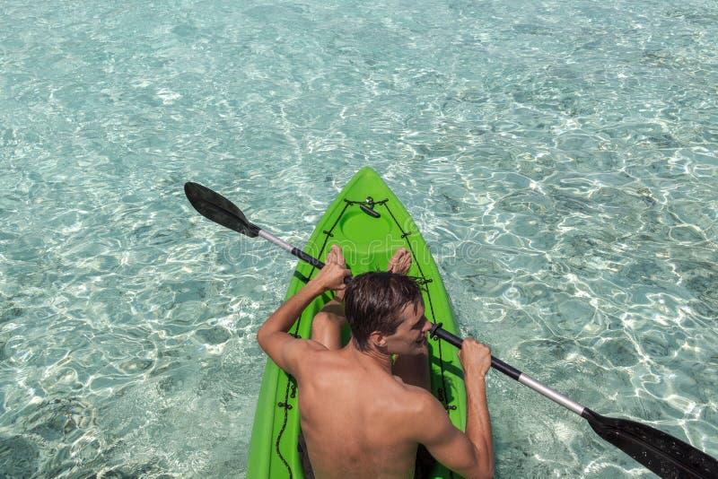 Junger gl?cklicher Mann, der auf einer Tropeninsel in den Malediven Kayak f?hrt Freies blaues Wasser lizenzfreie stockfotografie