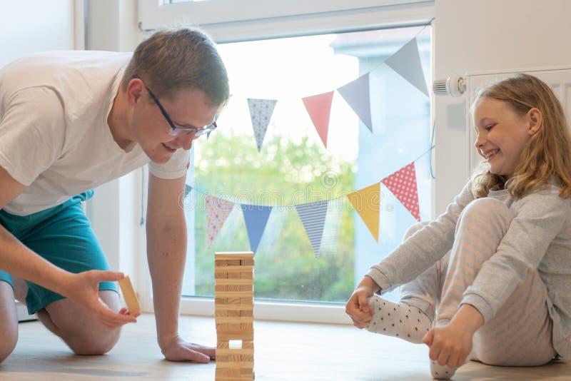 Junger gl?cklicher Vater, der mit seiner netten Tochter mit Holzkl?tzen spielt lizenzfreies stockfoto