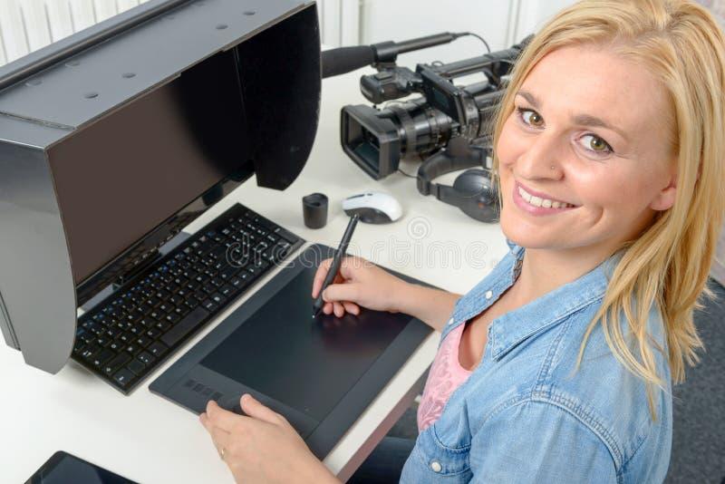 Junger Grafikdesigner, der an Computer unter Verwendung der Tablette arbeitet stockfotos