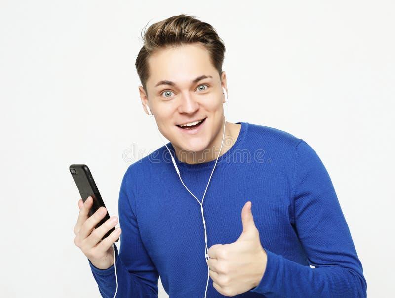 Junger gut aussehender Mann auf wei?em Studiohintergrund h?rend Musik auf Kopfh?rern stockfoto