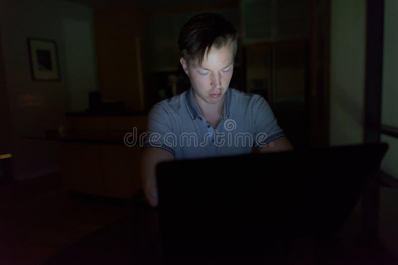 Junger gut aussehender Mann, der Laptop im dunklen Wohnzimmer verwendet lizenzfreie stockfotografie