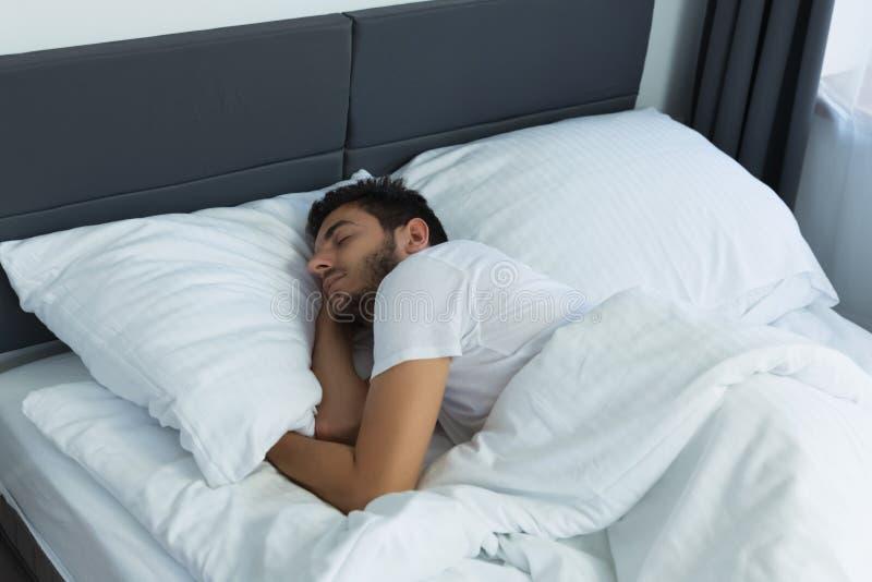 Junger gut aussehender Mann, der in seinem Bett schläft lizenzfreie stockfotografie