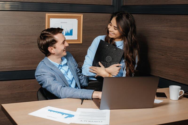 Junger gut aussehender Mann des Fotos, der mit ihrem Kollegen im modernen Büro flirtet lizenzfreie stockfotografie
