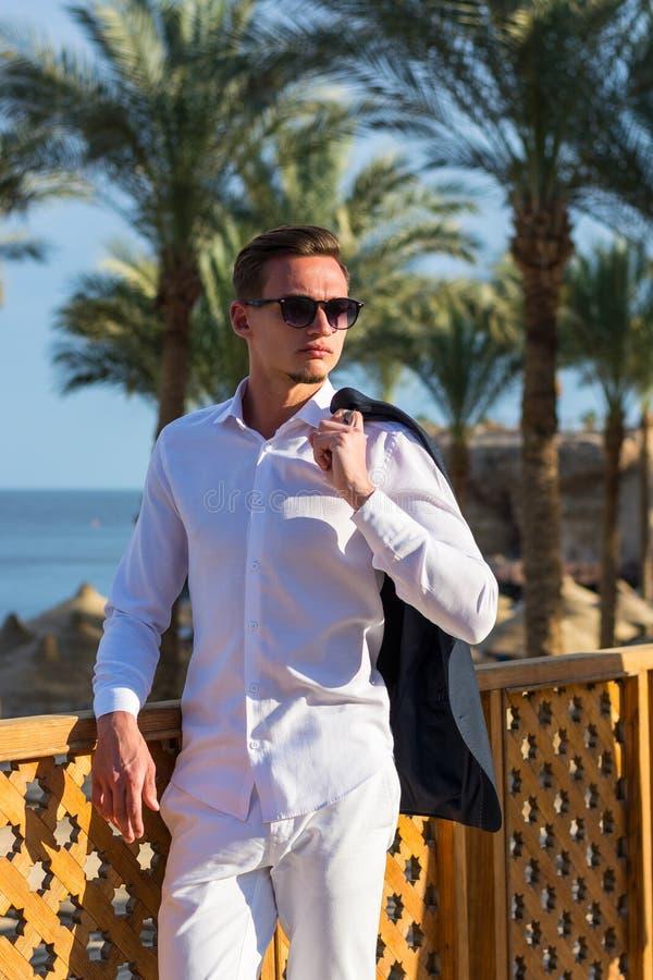 Junger gut aussehender Mann in einem weißen Hemd, in einer Jacke und in weißen Hosen am Seehintergrund und an den Palmen lizenzfreies stockfoto