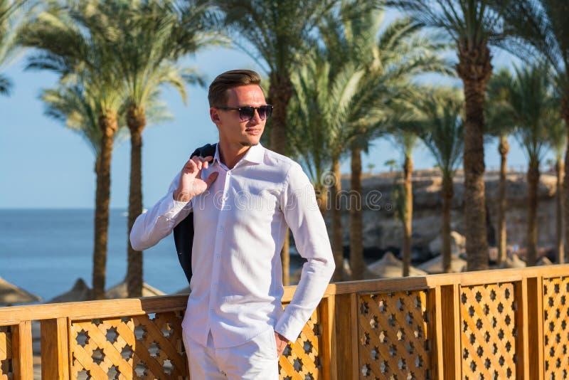 Junger gut aussehender Mann in einem weißen Hemd, in einer Jacke und in weißen Hosen am Seehintergrund und an den Palmen lizenzfreie stockfotos